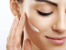 Woman putting facial moisturizer on face