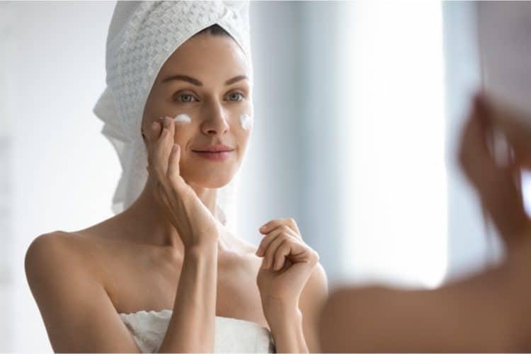 Woman applying facial moisturizer